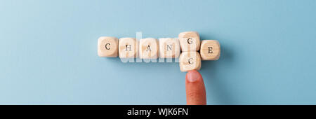 Word Change spelled on wooden dices with male finger replacing the letter G wit letter C to spell the word Chance. Over blue background.