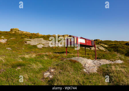 Red painted mountain rescue supply box on green hillside above Bergen, Norway, probably holding first aid kit and stretcher - Stock Photo