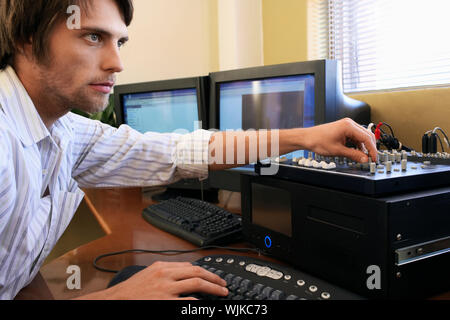 Male sound engineer using computer keyboard and adjusting knob on mixer in studio - Stock Photo