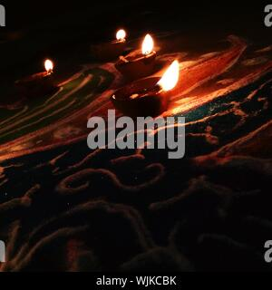 Close-up Of Illuminated Diyas On Rangoli - Stock Photo