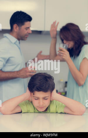 Sad young boy covering ears while parents quarreling in the kitchen at home - Stock Photo