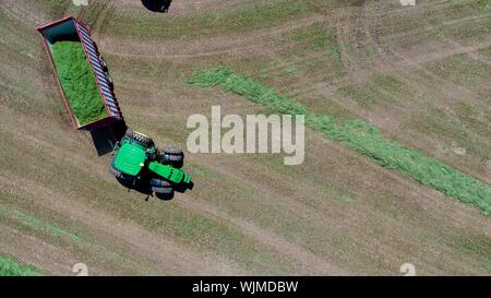 Aerial view, directly above, of John Deere tractor pulling hay wagon, on farm alfalfa field outside Monroe, Wisconsin, USA - Stock Photo