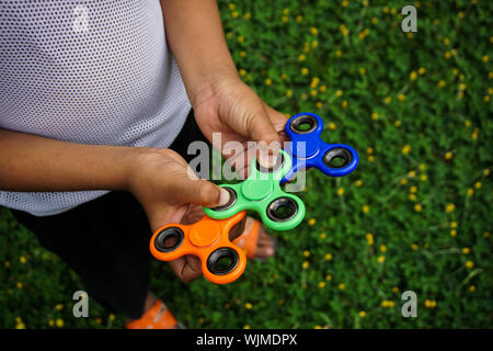 Low Section Of Man Holding Colorful Fidget Spinners On Grassy Field - Stock Photo