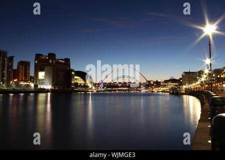 Illuminated Gateshead Millennium Bridge Over River Tyne Against Sky - Stock Photo