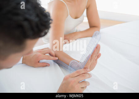 Physiotherapist examining patients wrist with goniometer in office - Stock Photo