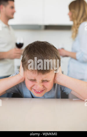 Furstrated boy covering ears while parents arguing in background at home - Stock Photo