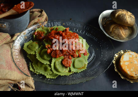High Angle View Of Spinach Ravioli With Red Marinara Sauce In Plate On Table - Stock Photo