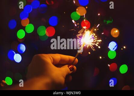 Cropped Hand Of Woman Holding Lit Sparkler At Night - Stock Photo