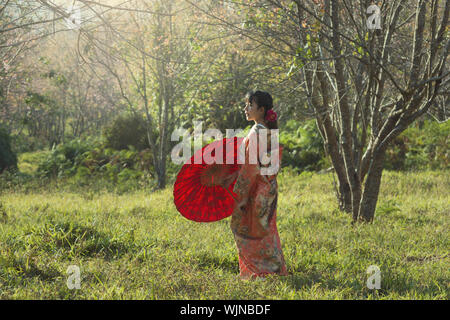 Woman Wearing Kimono Holding Red Umbrella Standing On Grass In Forest - Stock Photo