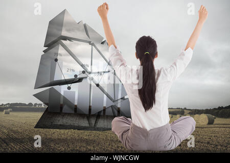 Businesswoman sitting cross legged cheering against landscape with bales of straw - Stock Photo