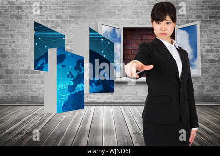 Focused businesswoman pointing against window frame on red brick wall - Stock Photo