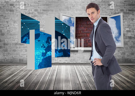 Serious businessman with hands on hips against window frame on red brick wall - Stock Photo