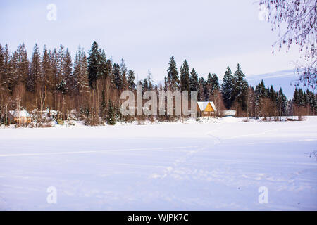 Winter landscape with a small house in the forest - Stock Photo