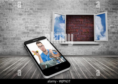 It technician on smartphone screen against window frame on red brick wall - Stock Photo