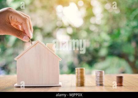 Cropped Hand Inserting Coin In Piggybank On Table - Stock Photo