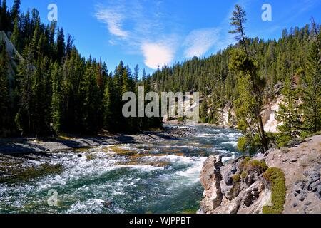 Scenic View Of Waterfall In Forest Against Sky - Stock Photo