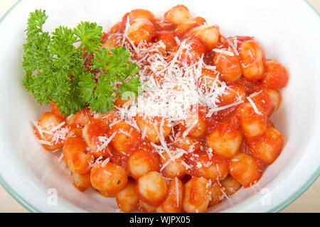 Top view white bowl with green ring around edge with fresh homemade gnocchi covered in marinara sauce and garnished with fresh grated parmesan cheese - Stock Photo