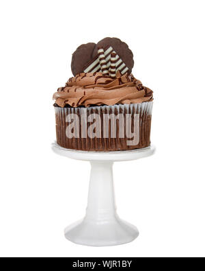 Giant chocolate cup cake with chocolate frosting, candy and cookies embellishing sitting on a white pedestal isolated on white. - Stock Photo