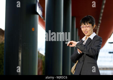 Asian business woman traveller on a trip at the train station - Stock Photo
