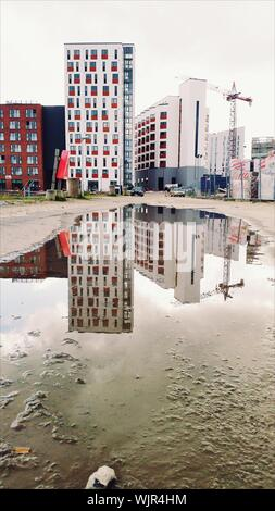Reflection Of Building In Water Collected On Ground - Stock Photo