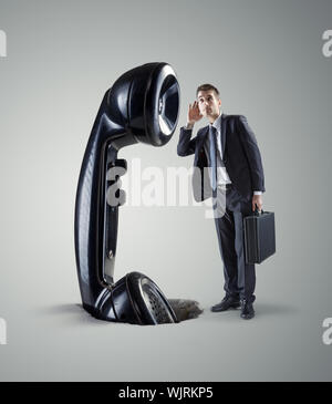 Young businessman and huge retro phone receiver. - Stock Photo