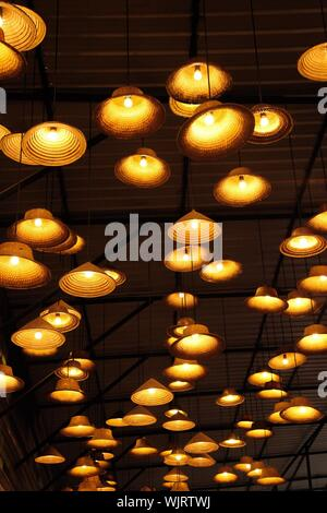 Low Angle View Of Illuminated Pendant Lights Hanging From Ceiling - Stock Photo