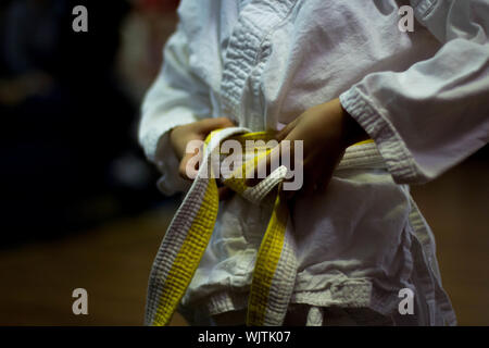 Midsection View Of Person Tying Karate Belt - Stock Photo