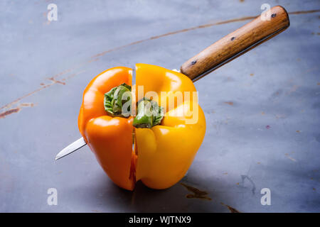 Close-up Of Knife With Yellow And Orange Halved Bell Peppers On Table