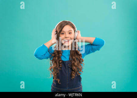 Feeling the beauty of the song. Cute small child listening to song on blue background. Adorable little girl enjoying song playing in headphones. Composing a song. - Stock Photo
