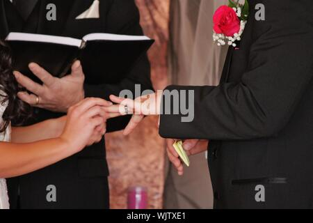 Bride And Groom Exchange Rings In Church At Wedding Ceremony - Stock Photo