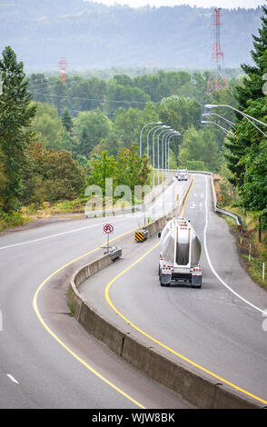 Big rig powerful professional industrial grade bonnet semi truck transporting commercial cargo in bulk conical semi trailers running on the turning ro - Stock Photo