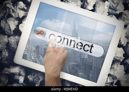 Hand touching the word connect on search bar on tablet screen on crumpled papers - Stock Photo