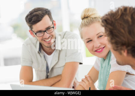Closeup of a group of casual people working in a bright office - Stock Photo