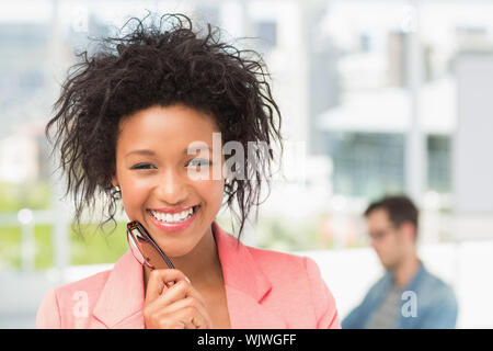 Closeup portrait of a casual female artist with colleague in the background at a bright office - Stock Photo