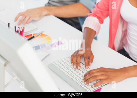 Closeup mid section of a casual young couple working on computers in a bright office - Stock Photo