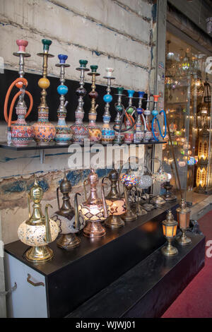 There are hookahs and teapots on the shelves placed in front of the old wall. - Stock Photo