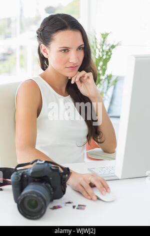 Focused photographer sitting at her desk using computer in creative office - Stock Photo