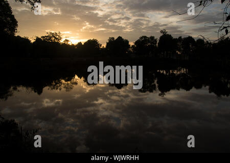 Refletion of the sunset sky over lake surface - Stock Photo