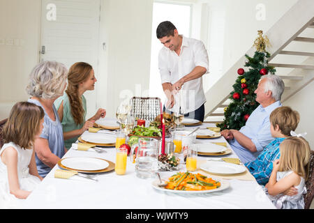 Father serving Christmas meal to family at dining table - Stock Photo