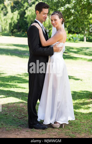 Full length of young newly wed couple embracing in garden - Stock Photo
