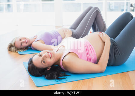 Smiling pregnant women in yoga class lying on mats in a fitness studio - Stock Photo