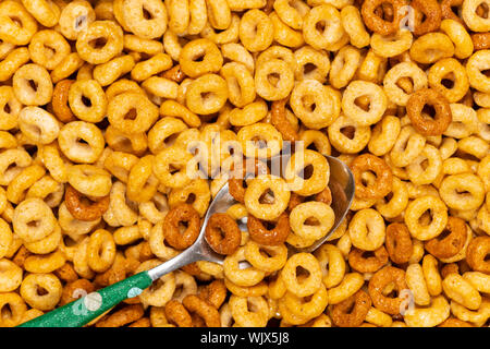 Close-up texture of toasted oats cereal in a metal spoon with selective focus. - Stock Photo