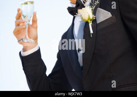 Close-up mid section of beautiful flowers on lapel of male as he holds champagne glass - Stock Photo