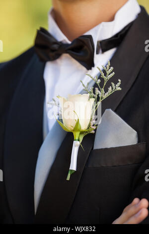 Close-up mid section of beautiful flowers on lapel of male - Stock Photo