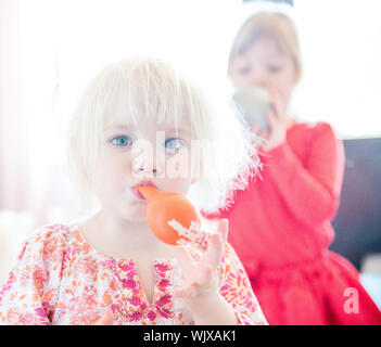 Portrait Of Cute Girls Blowing Balloons - Stock Photo