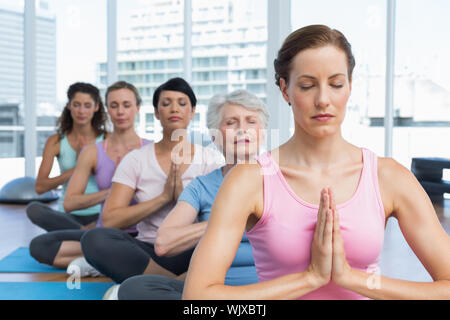 Female trainer and class sitting with joined hands in a row at yoga class