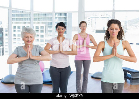 class standing in namaste pose at yoga class stock photo