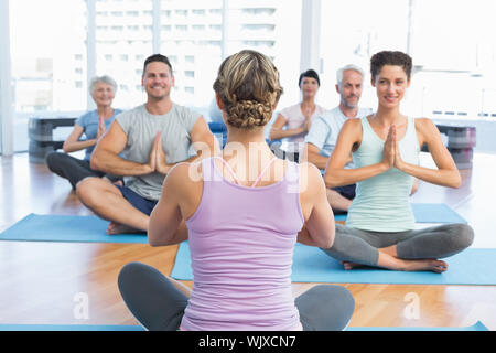 Sporty people with joined hands sitting at fitness studio