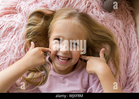 Adorable little girl with long blonde hair lying on pink fur blanket and showing teeth. Positive emotions , expression, fun. Beautiful child. Happy - Stock Photo