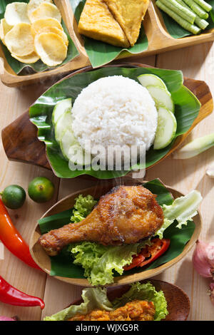 Popular Indonesian local food nasi ayam penyet, indonesian fried chicken rice. Fresh hot with steam smoke. - Stock Photo